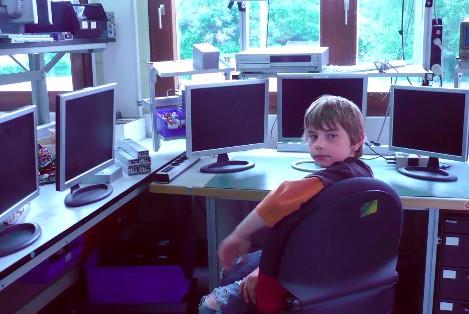Junge macht Praktikum, sitzt vor Bildschirmen
